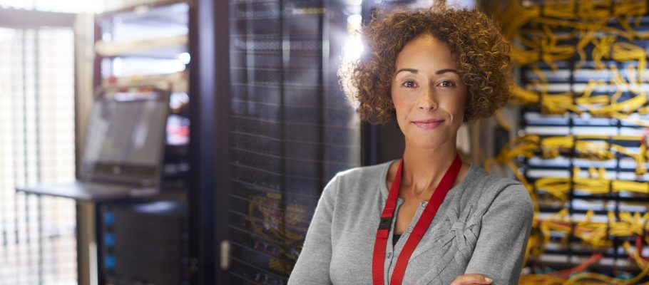a female IT technician is editing the programme on the network server in a server room. She is looking to camera and smiling as she stands amongst the banks of servers and cables.